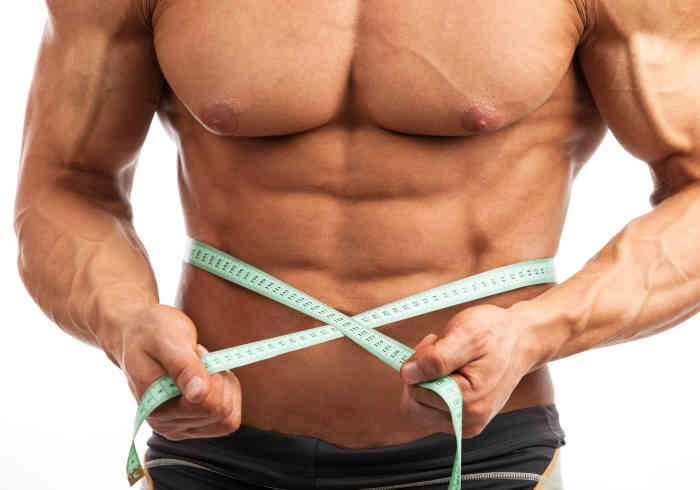 Young muscular man with measuring tape around his waist | Does MK-677 Cause Water Retention