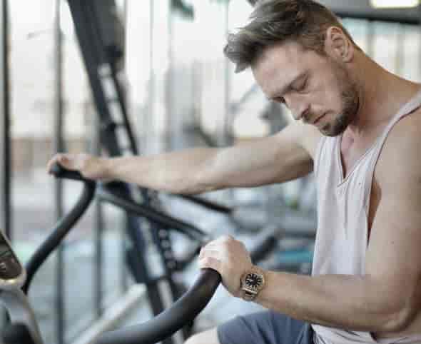 man tired resting on gym machine: does mk-677 improve sleep quality