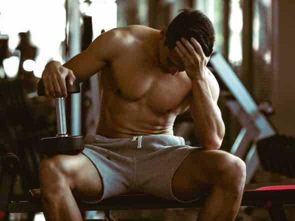 young strong sporty man with big dumbbell : does MK677 cause headaches