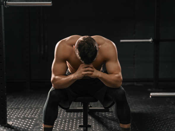 strong sporty man sitting on gym bench suffering anxiety